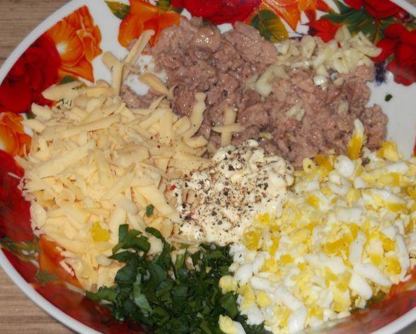 Подготовленные ингредиенты салата из печени трески в большой тарелке