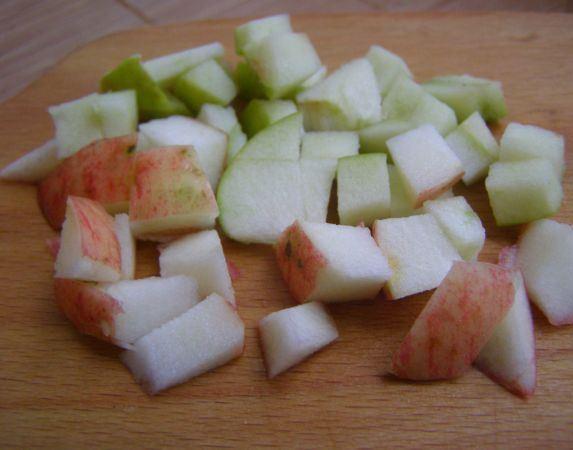 Нарезанные маленькими кубиками свежие яблоки на разделочной доске