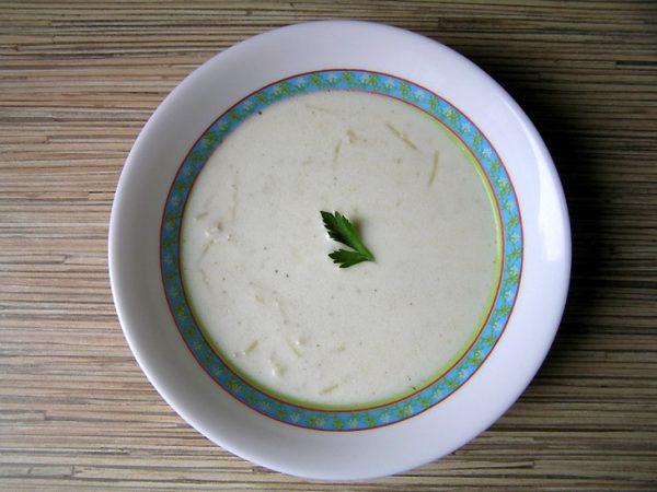 Молочный суп с вермишелью, курицей и свежей петрушкой в тарелке на деревянной поверхности