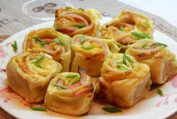 Закуска из слоёного теста с варёной колбасой, сыром и зеленью на тарелке с узорами