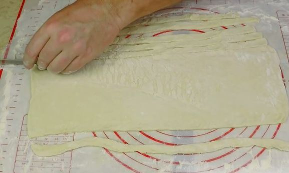 Нарезка раскатанного слоёного теста на длинные тонкие полоски