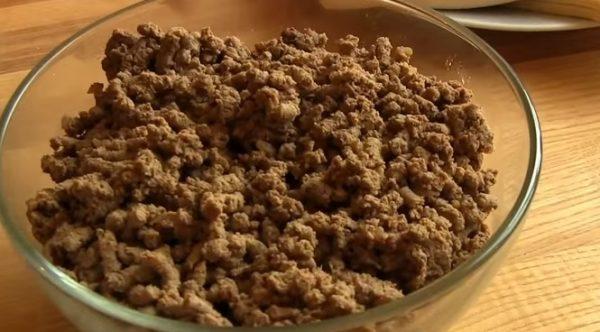 Прокрученная через мясорубку готовая куриная печень в стеклянной миске на столе