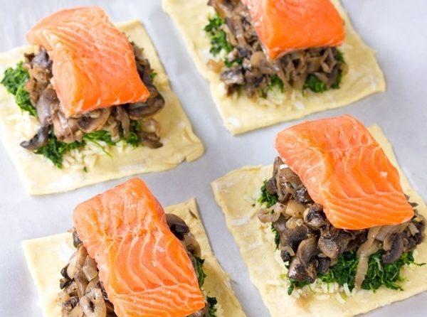 Кусочки сырого теста со шпинатом, грибами и красной рыбой