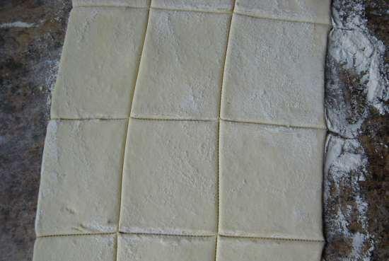 Разрезанный на порционные куски лист слоёного теста на столе