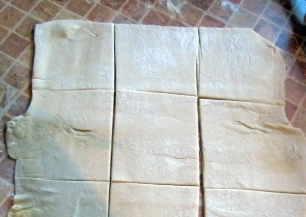 Разрезанный на квадраты лист слоёного теста на рабочей поверхности кухонного стола