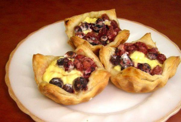 Закусочные корзиночки из слоёного теста с творогом и ягодами на красивой тарелке