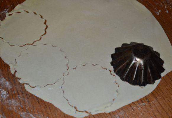Сырое тесто на столе с мукой и металлическая формочка для порционного кекса