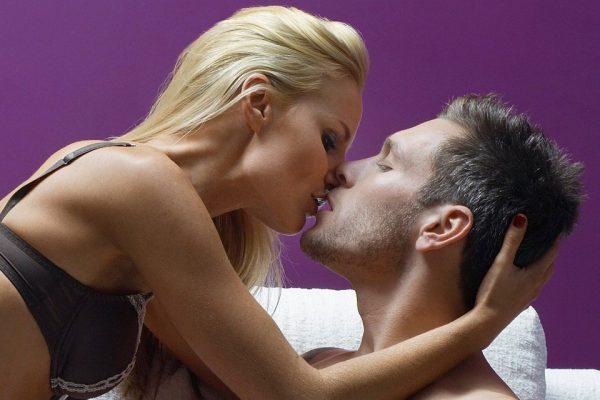Мужчина и женщина целуются в постели