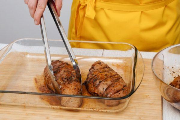 Заготовки из сырого куриного филе со специями в стеклянной форме для запекания