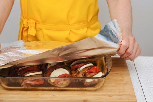 Стеклянная форма с заготовками из куриного филе под листом фольги для запекания