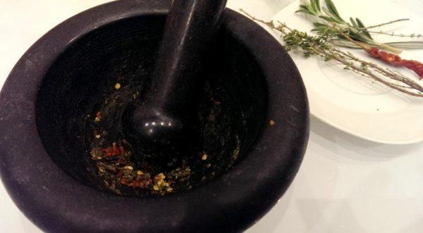 Чёрная ступка с пестиком и растёртыми продуктами