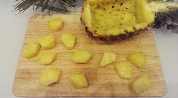 Половинка ананаса с вырезанной мякотью и кусочки фрукта на деревянной разделочной доске