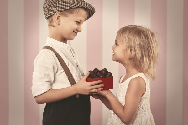 Мальчик дарит девочке конфеты