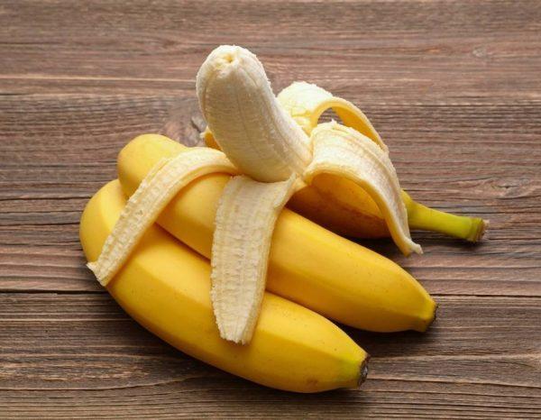 Наполовину очищенный банан лежит на двух других