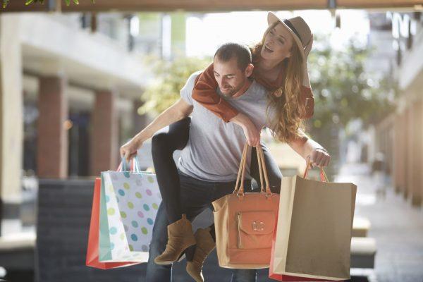 Мужчина несёт сумки и женщину