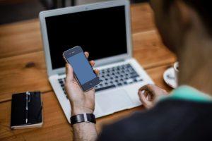Мужчина, сидящий за ноутбуком, держит в руке телефон с погасшим экраном