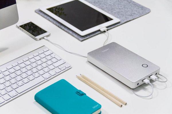 Смартфон и планшет, лежащие на столе, заряжаются от внешнего аккумулятора