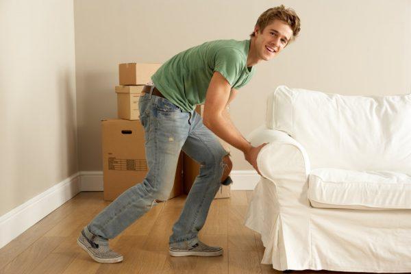 Мужчина двигает мебель