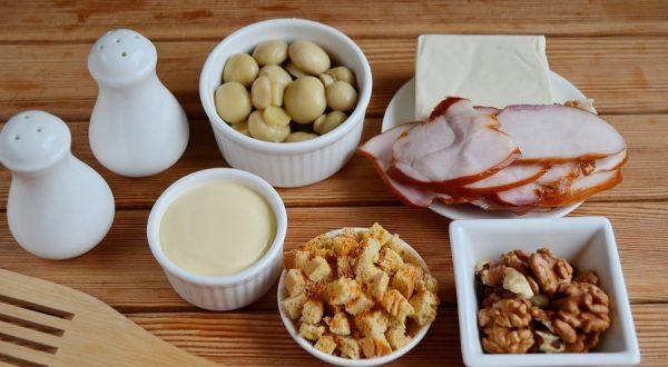 Продукты для приготовления салата с копчёной куриной грудкой, грибами и сухариками на столе