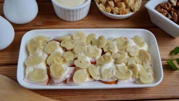 Копчёная куриная грудка и маринованные шампиньоны с майонезом на белой прямоугольной тарелке