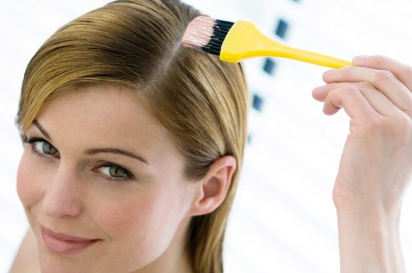 Женщина наносит маску на волосы