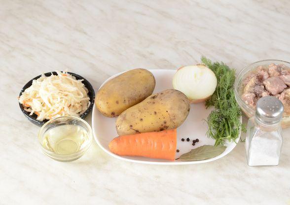 Продукты для приготовления щей с кислой капустой и тушёнкой на столе