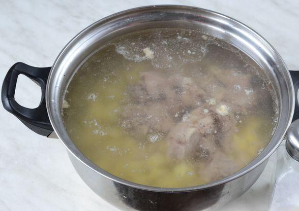Нарезанный кубиками картофель и кусочки мяса в кастрюле с водой