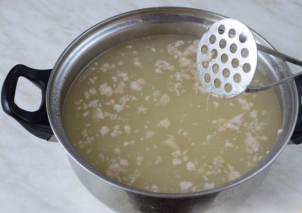 Кастрюля я супом и металлическая толкушка для картофеля