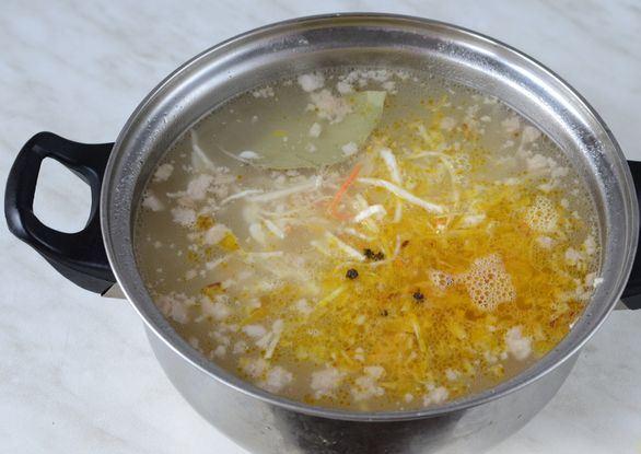 Кастрюля с супом, овощной зажаркой, лавровым листом и горошинами чёрного перца