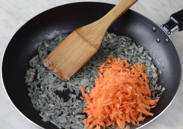 Обжаренный репчатый лцук и тёртая морковь в чёрной сковороде с деревянной лопаточкой