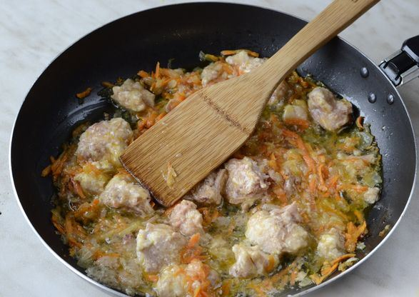Обжаренные овощи с кусочками свиной тушёнки в сковороде с деревянной лопаточкой