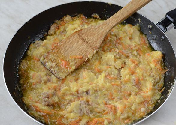 Гороховое пюре с тушёнкой в чёрной сковороде с деревянной лопаточкой