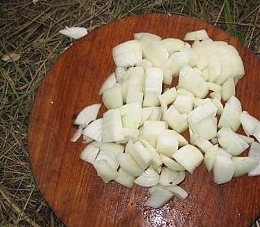 Нарезанный репчатый лук на круглой разделочной доске из дерева
