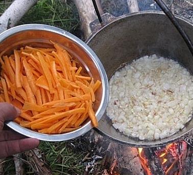 Репчатый лук в казане над костром и нарезанная соломкой морковь в металлической миске