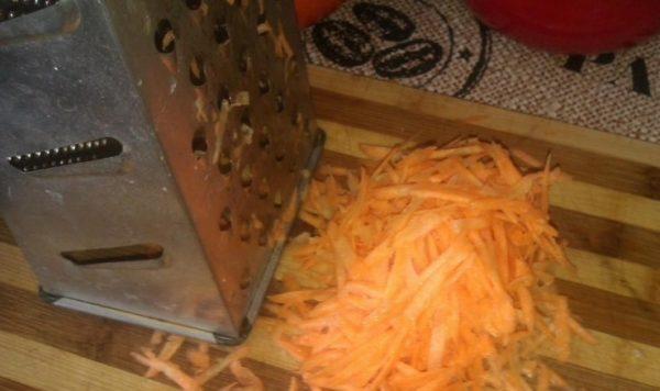 Тёртая морковь и металлическая тёрка на полосатой разделочной доске