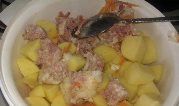 Нарезанный кубиками сырой картофель с кусочками тушёнки, рубленым репчатым луком и тёртой морковью в белой ёмкости