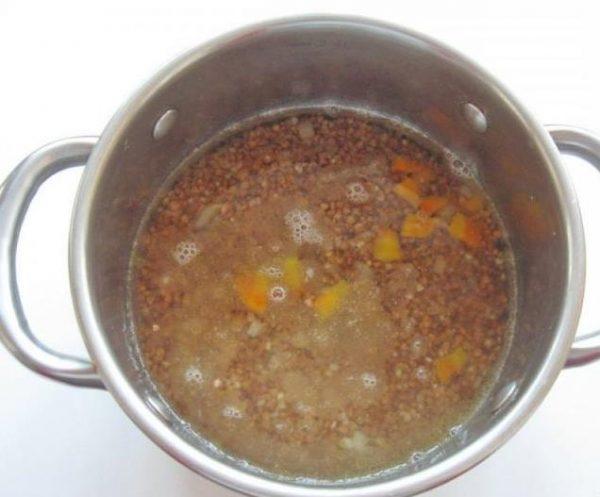 Гречневая крупа в кастрюле с кусочками овощей и водой