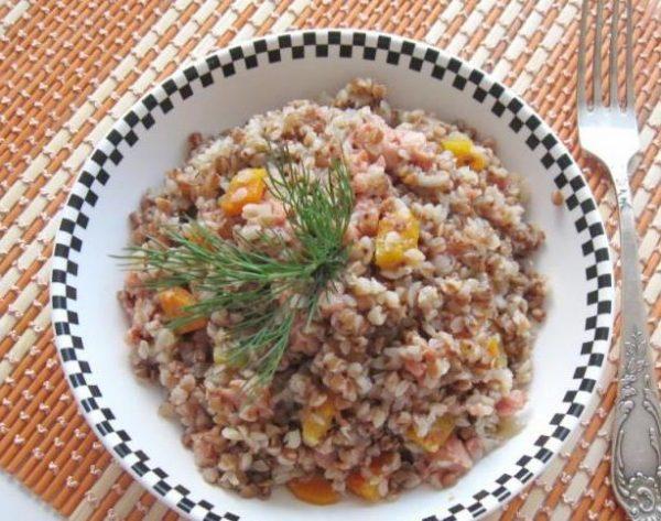 Гречневая кашу со свиной тушёнкой, овощами и свежим укропом в порционной тарелке на столе
