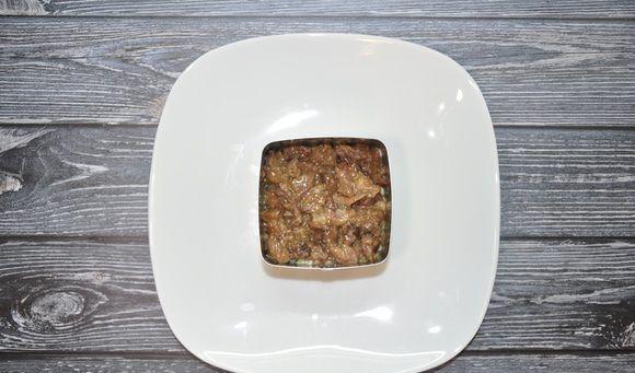 Свиная тушёнка в квадратном форме на белой тарелке