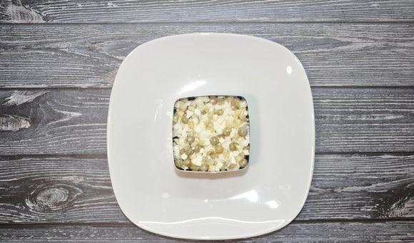 Слой из смеси консервированного горошка, солёных огурцов и яиц в квадратной металлической формочке на белой тарелке