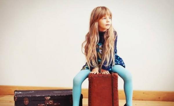 Девочка сидит на чемодане
